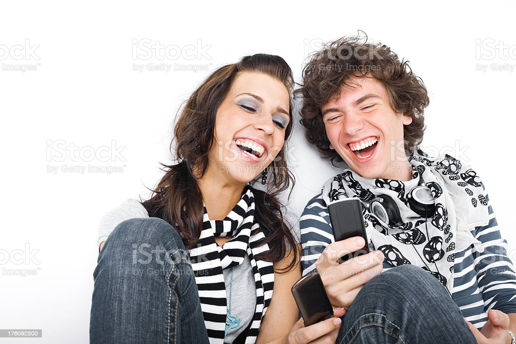 Two Teens Texting Together Laughing royalty-free stock photo