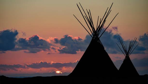 zwei tipi-silhouetten bei lila sonnenuntergang - indianer tipi stock-fotos und bilder