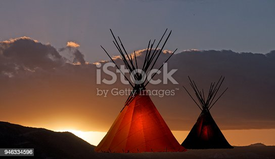Two prairie First Nation teepee with interior light at sunset.
