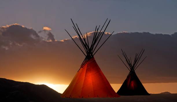 zwei tipis bei sonnenuntergang - indianer tipi stock-fotos und bilder