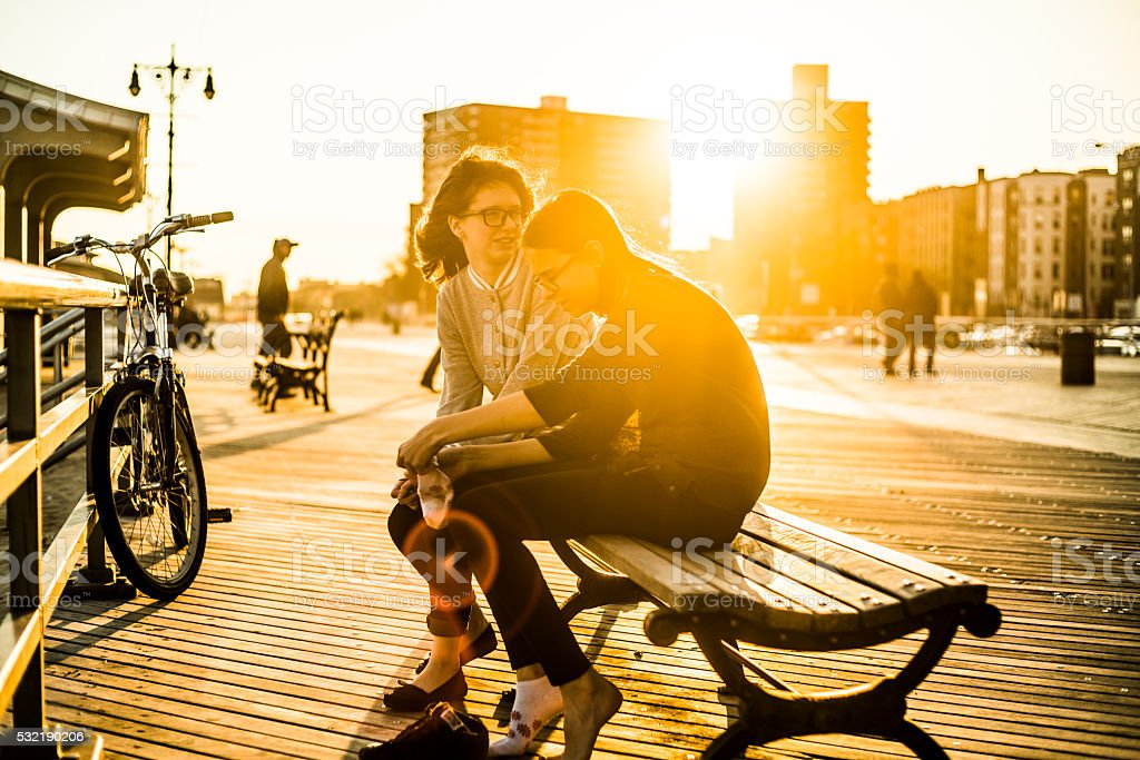 Two tennager girls sitting on bench at Coney Island broadwalk stock photo