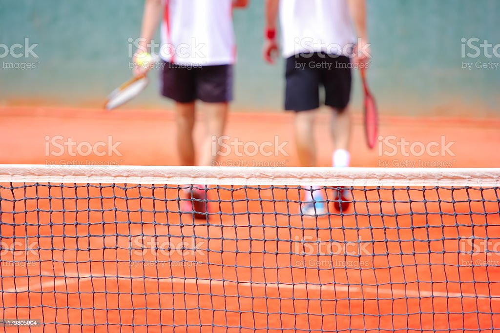 Two tennis players walking away after a match stock photo