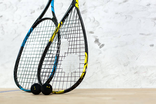 Two tennis rackets and balls standing by the wall stock photo