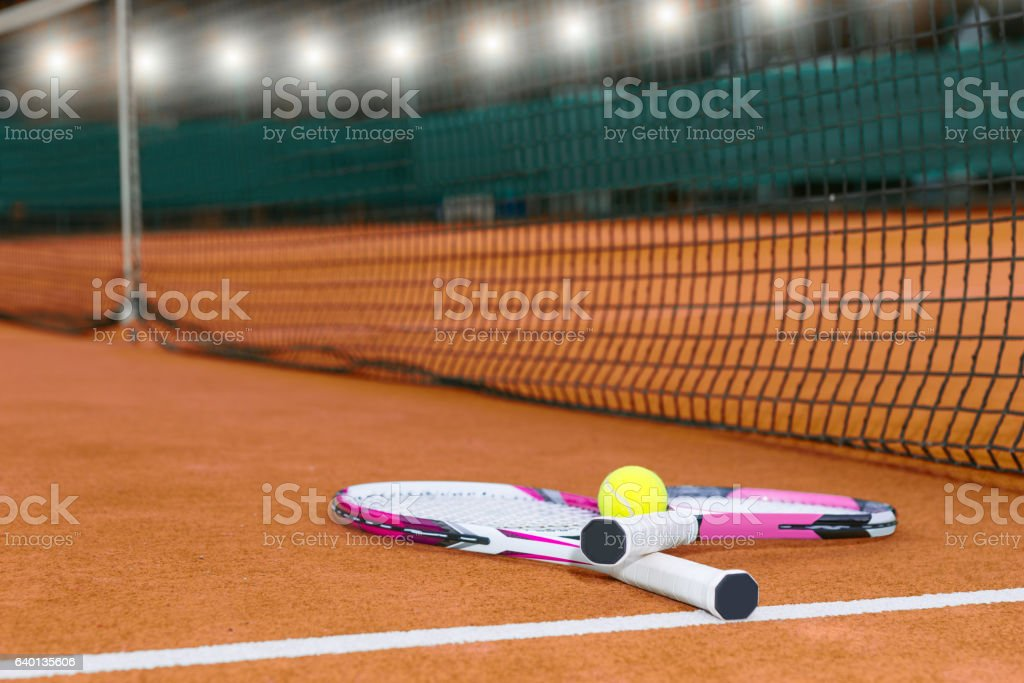 Two tennis rackets with a tennis ball lying near net stock photo