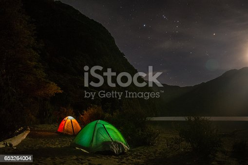 Campsite next to a lake / Tents lighten up from inside