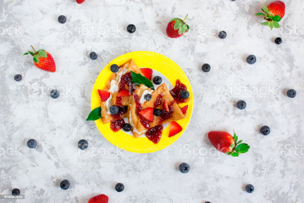 Two thin pancakes, folded in triangles, are poured with sour cream, jam and decorated with fresh berries surrounded by blueberries and strawberries. The concept of Russian holiday Maslenitsa stock photo