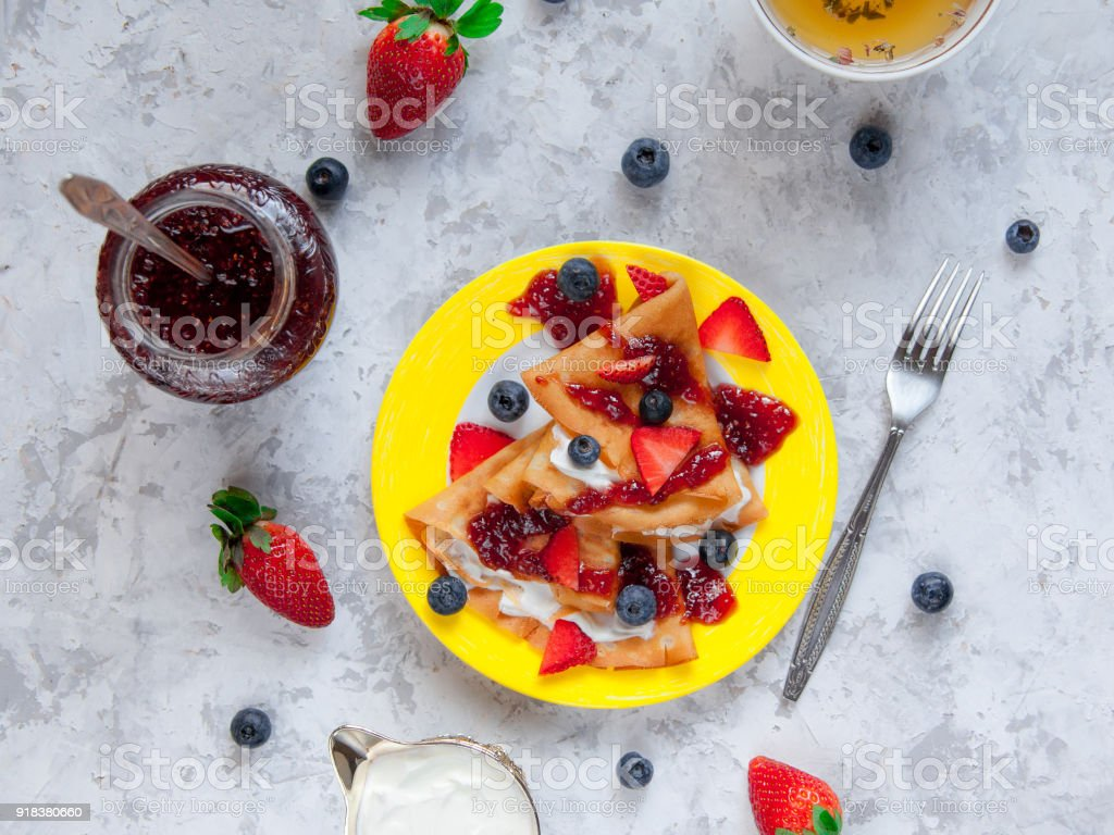 Two thin pancakes, folded in triangles, are poured with sour cream, jam and decorated with fresh berries. The concept of Russian holiday Maslenitsa stock photo
