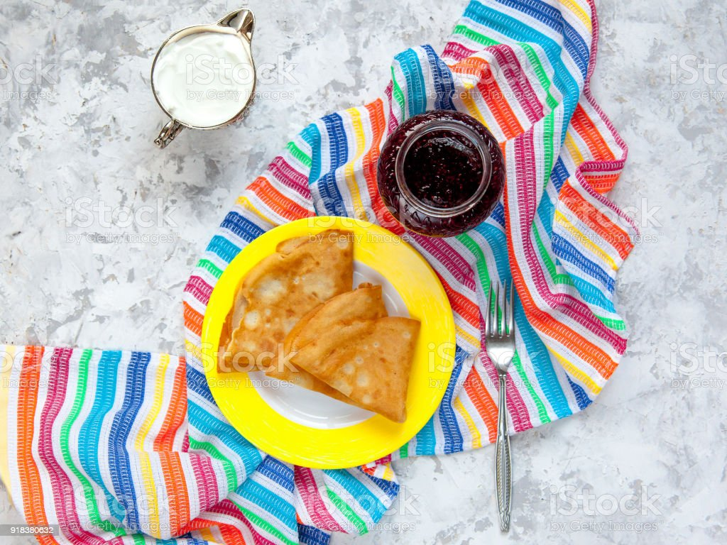 Two thin pancakes, folded in triangles on a yellow plate. The concept of Russian holiday Maslenitsa stock photo