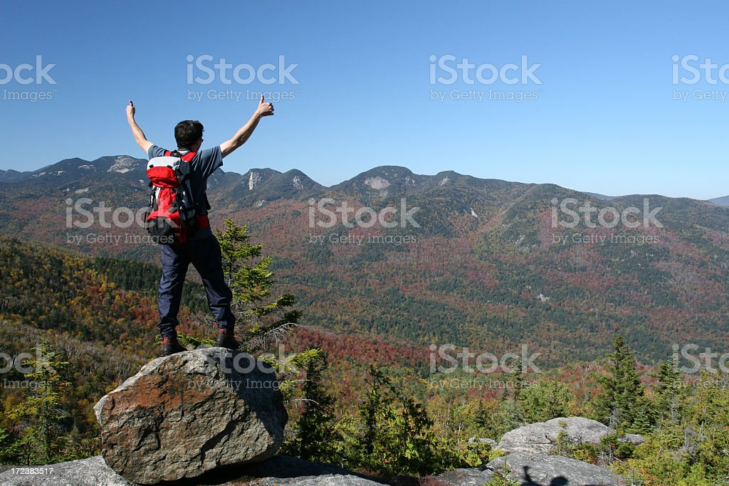 Two thumbs up hiker on summit against blue sky stock photo