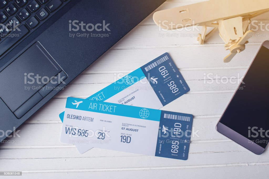 Two tickets are on the table with a phone and laptop. Concept of buying the online ticket booking for travel stock photo