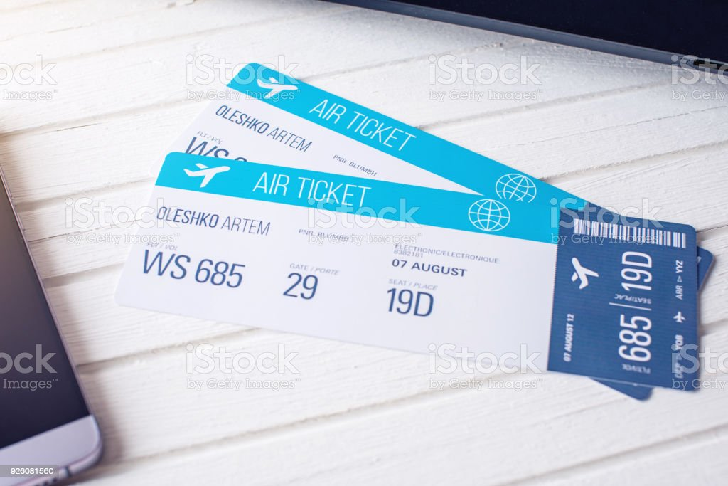 Two tickets are on the table with a phone. Concept of buying the online ticket booking for travel stock photo