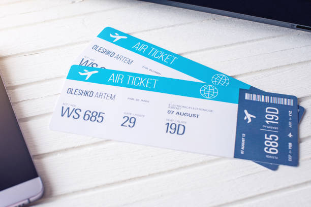 two tickets are on the table with a phone. concept of buying the online ticket booking for travel - aeroplane ticket stock photos and pictures