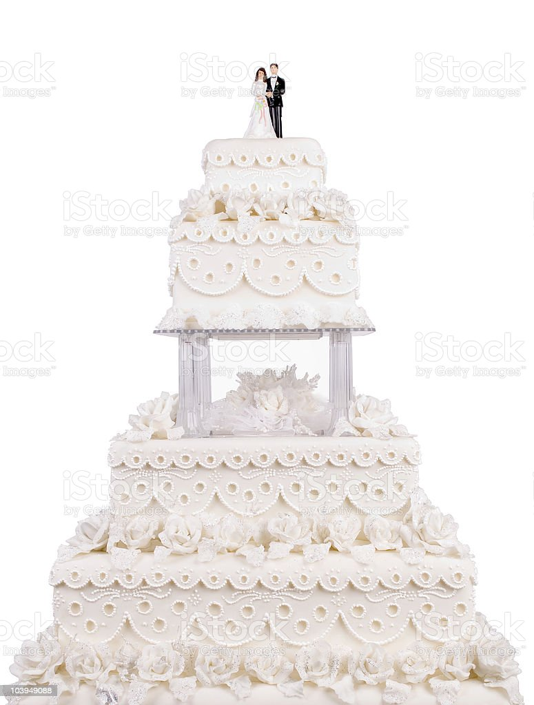 Two tier wedding cake with plastic couple on top stock photo