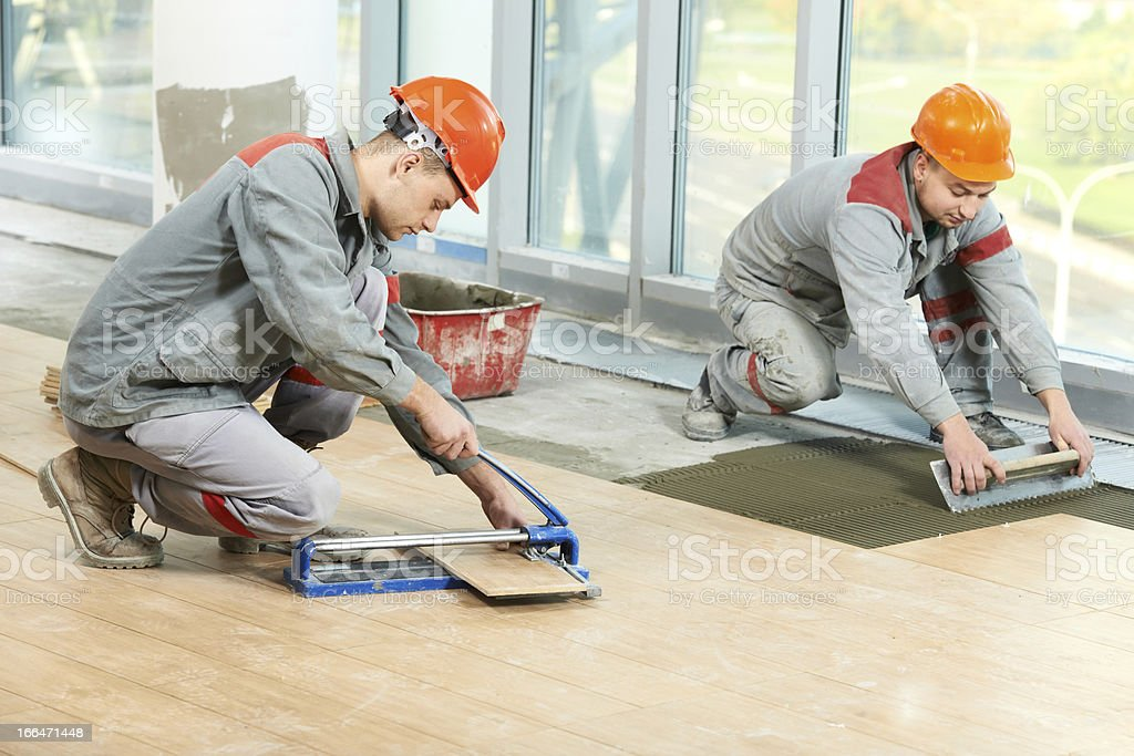 Two tilers at industrial floor tiling renovation stock photo