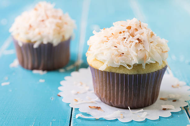 Two Toasted Coconut Topped Cupcakes on a Blue Table stock photo