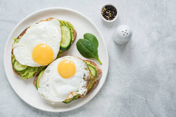 Two toasts with avocado, cucumber and egg stock photo