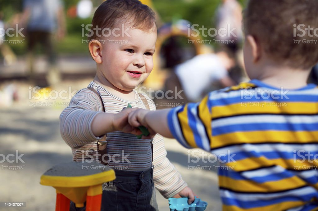 Two toddler boys hanging out on a playground stock photo
