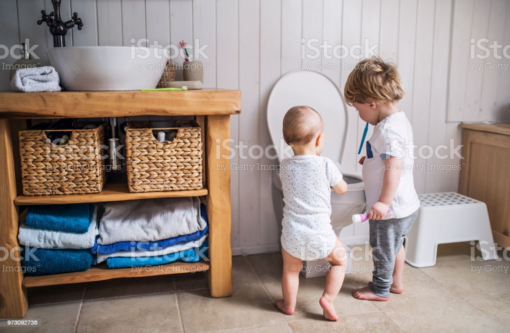 Two toddler children with toothbrush standing by the toilet in the bathroom at home. stock photo