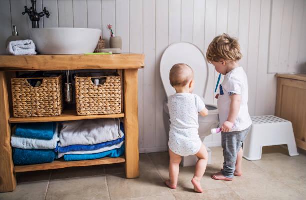Zwei Kleinkind Kinder Zahnbürste steht durch die Toilette im Badezimmer zu Hause. – Foto