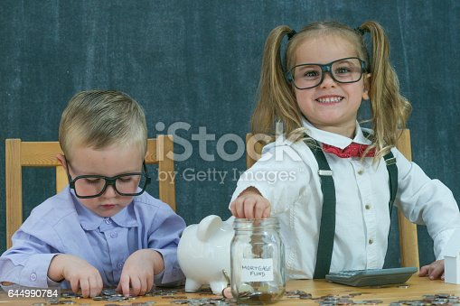 Two toddlers are dressed up as business adults. They are putting coins into a jar that says mortage fund on it.