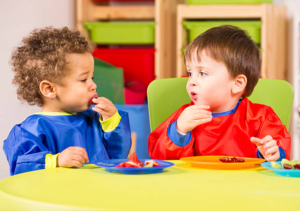 Two toddlers eating fruit in a nursery stock photo