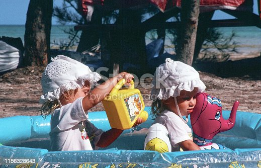 A horizontal image of 2 young children sitting in an inflatable pool near the ocean in the Florida Keys. They are in full sunlight and are wearing sunhats and t-shirts.