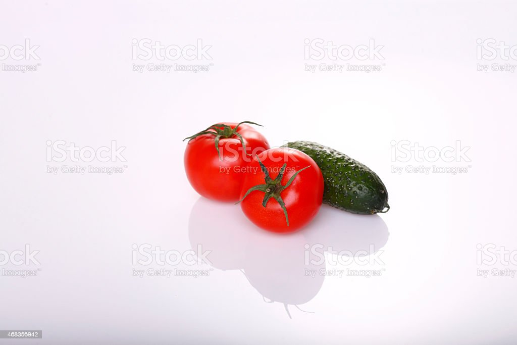 Two tomatoes and cucumber on white royalty-free stock photo