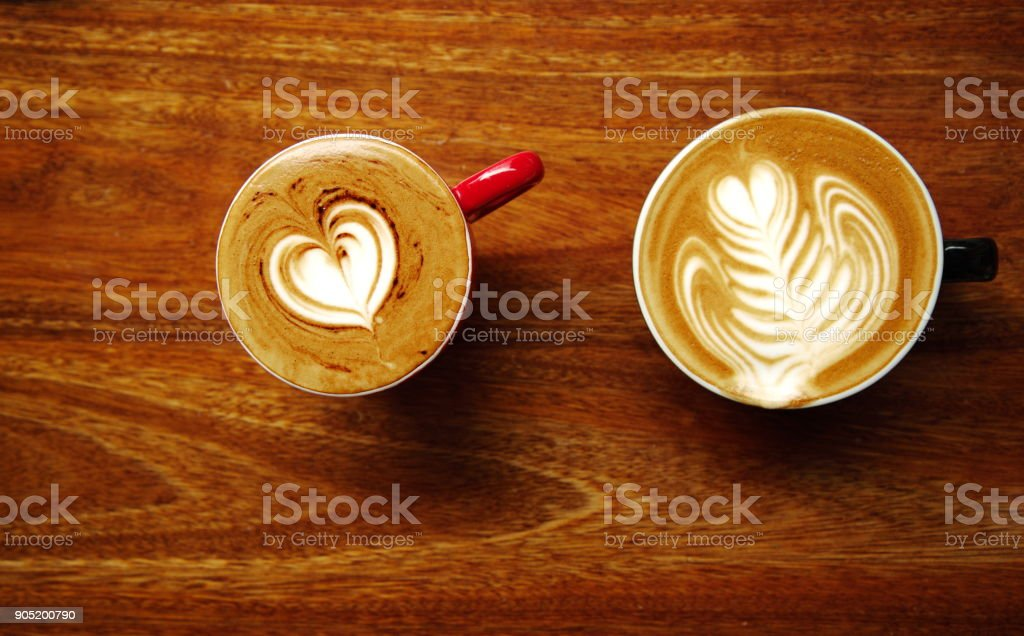 two top of latte art hot coffee cup on dark brown wood table background stock photo