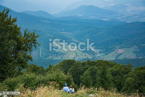 Two tourist girls sit on the mountainside and enjoy the scenery.
