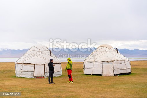 Two tourist having discussion in front of two yurts near Lake Song Kol, Kyrgyzstan.  It is cold, cloudy summer evening and is the final point of three days horseback riding over mountains from Kochkor to The Lake Song-Kul.
