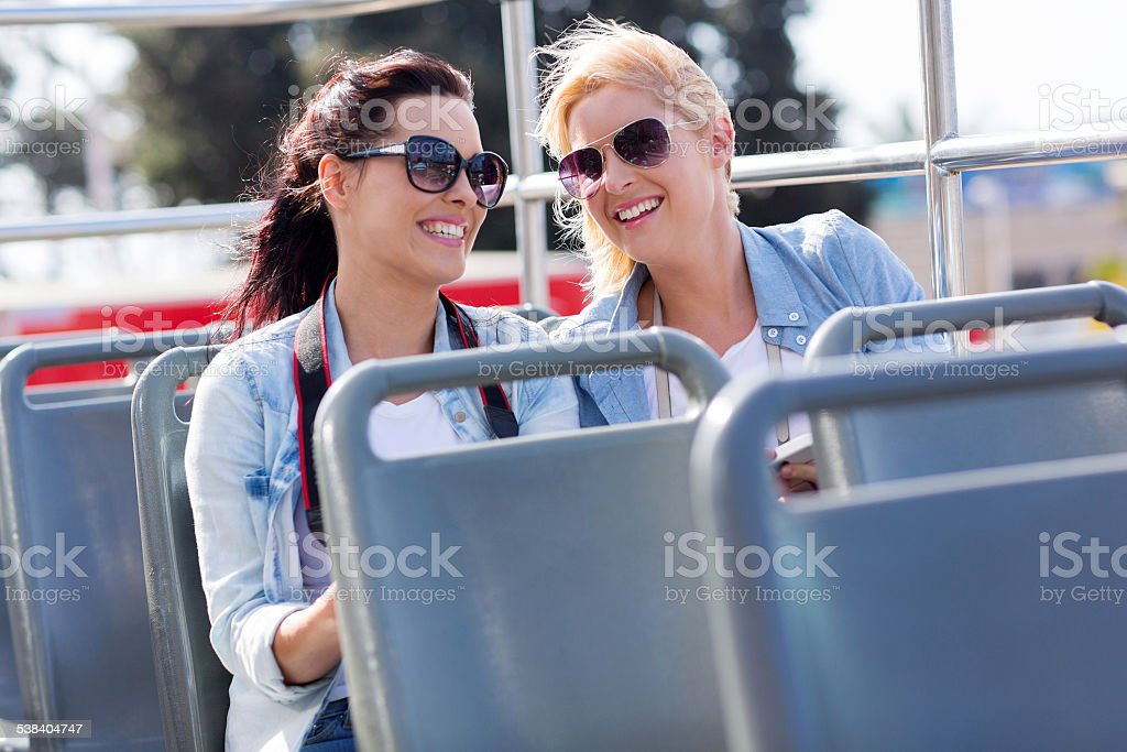 two tourists enjoying open top bus tour in the city stock photo