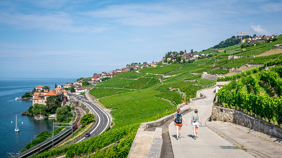 Two tourists hiking on a beautiful path in middle of Lavaux terraced vineyards and Rivaz village on Lake Geneva side in Lavaux Vaud Switzerland