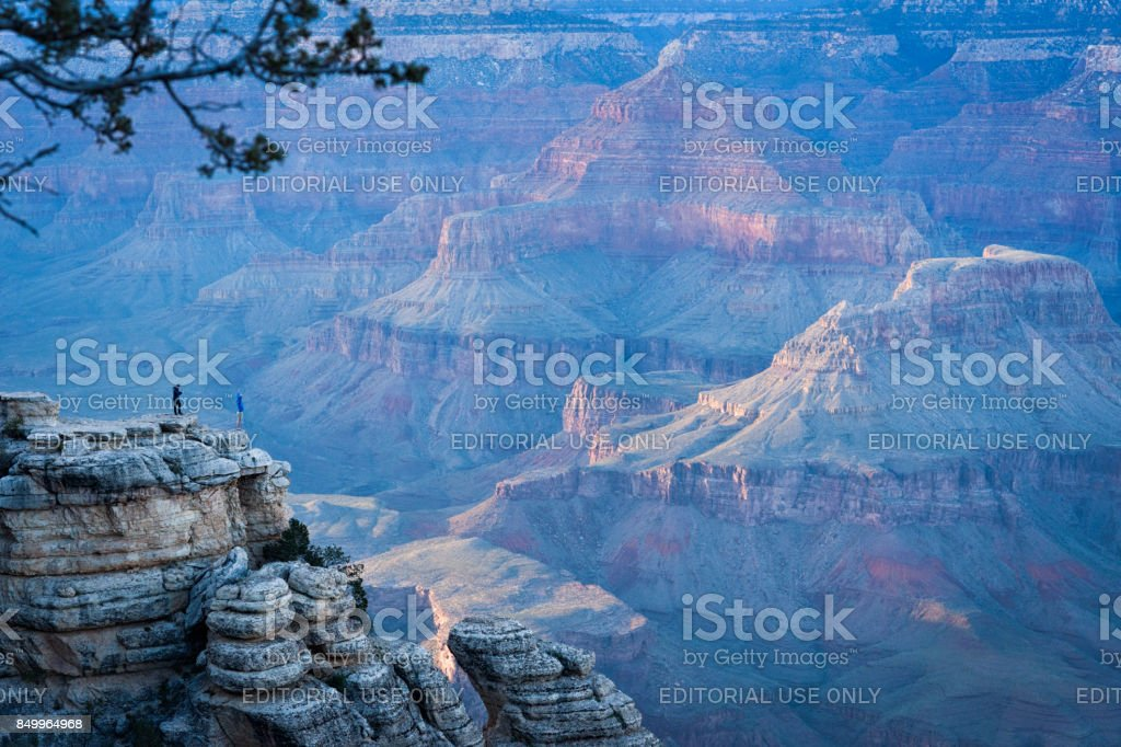 Two tourists overlook Grand Canyon at sunset stock photo