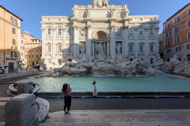 Two tourists take pictures in front of the deserted Trevi Fountain stock photo