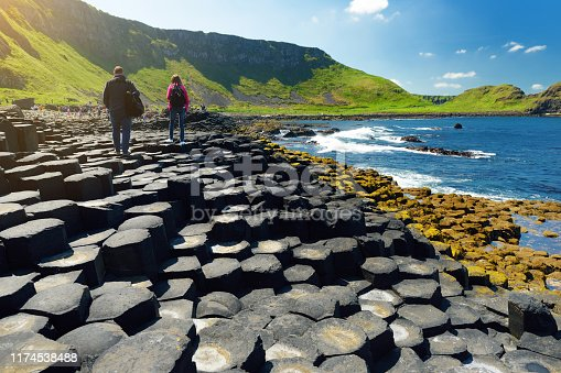 Two tourists walking at Giants Causeway, an area of hexagonal basalt stones, created by ancient volcanic fissure eruption, County Antrim, Northern Ireland. Famous tourist attraction, UNESCO World Heritage Site.
