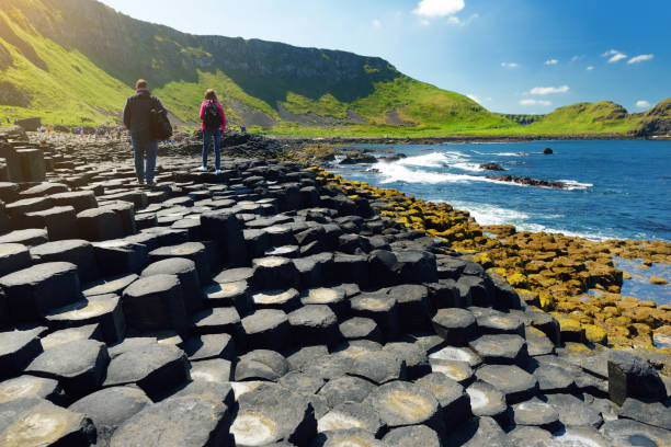 Two tourists walking at Giants Causeway, an area of hexagonal basalt stones, County Antrim, Northern Ireland. Famous tourist attraction, UNESCO World Heritage Site. stock photo