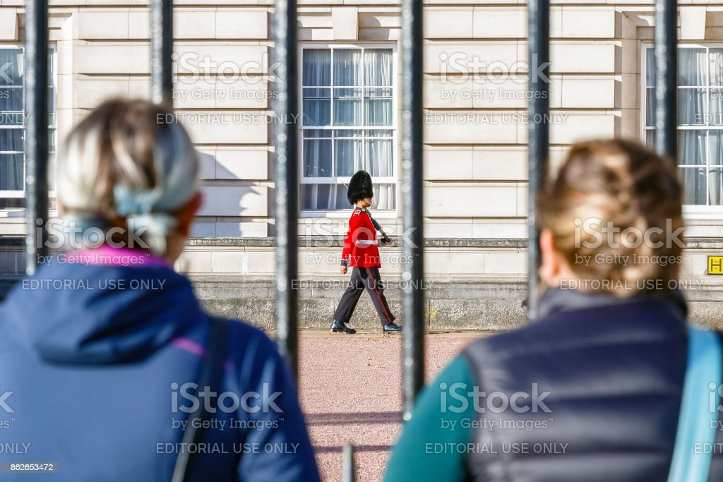 Two tourists watching a sentry of Grenadier Guards patrolling outside Buckingham Palace stock photo