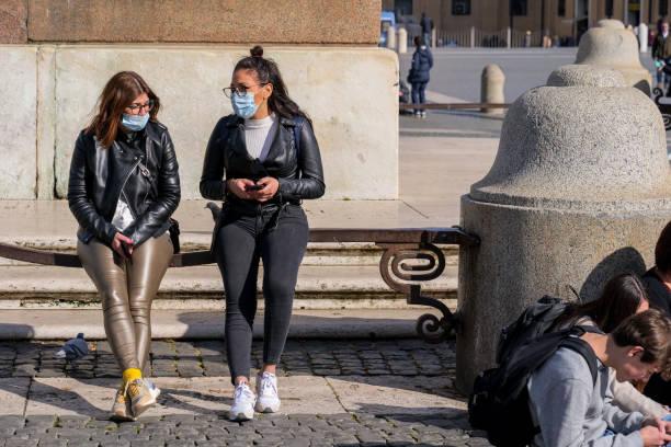 Deux touristes avec des masques médicaux sur leurs bouches sur la place Saint-Pierre - Photo