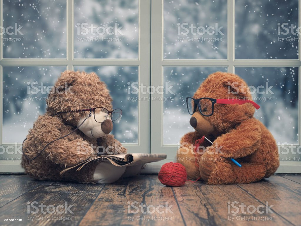 Two toy bears reading and crochet. As an old grandma and grandpa. Window. The snow falls, winter стоковое фото