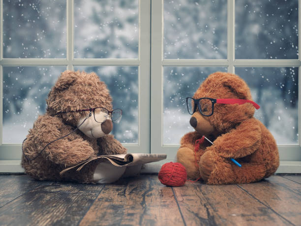 Two toy bears reading and crochet. As an old grandma and grandpa. Window. The snow falls, winter Two toy bears reading and crochet. As an old grandma and grandpa. Window. The snow falls, winter christmas teddy bear stock pictures, royalty-free photos & images