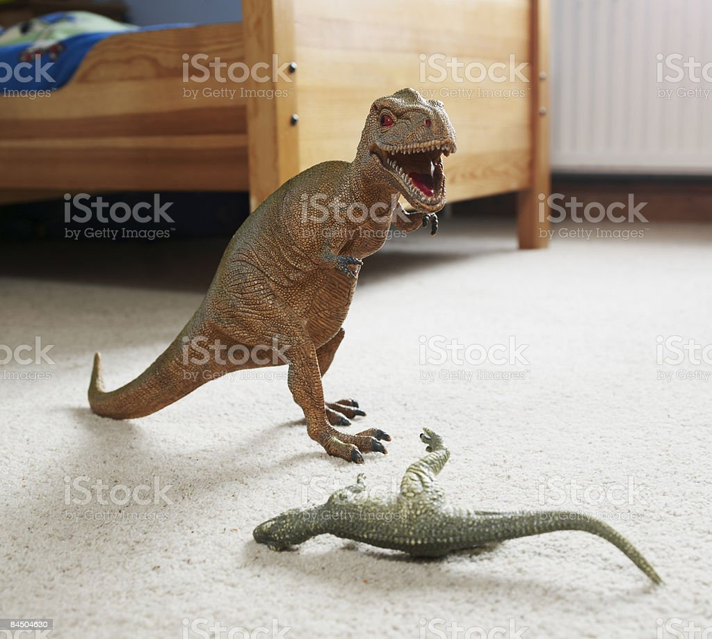 Two toy dinosaurs fighting in childs room royalty-free stock photo