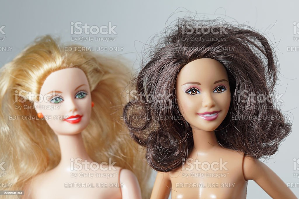 Two toy dolls Barbie and Teresa smiling friendly faces stock photo