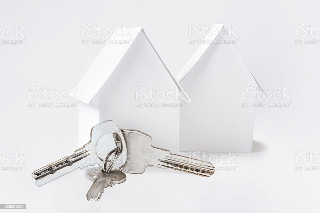 Two toy houses and keys on white background. stock photo