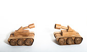 two toy tanks made by children from corrugated cardboard are fighting. toy cardboard tanks isolated on a white background. February 23. Men's day.