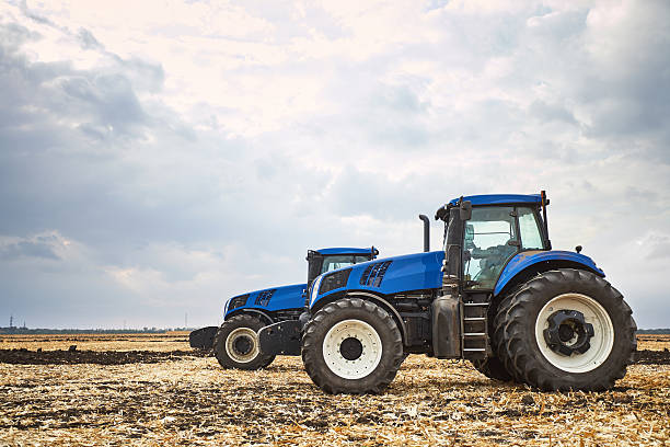 Two tractor cultivating the land stock photo