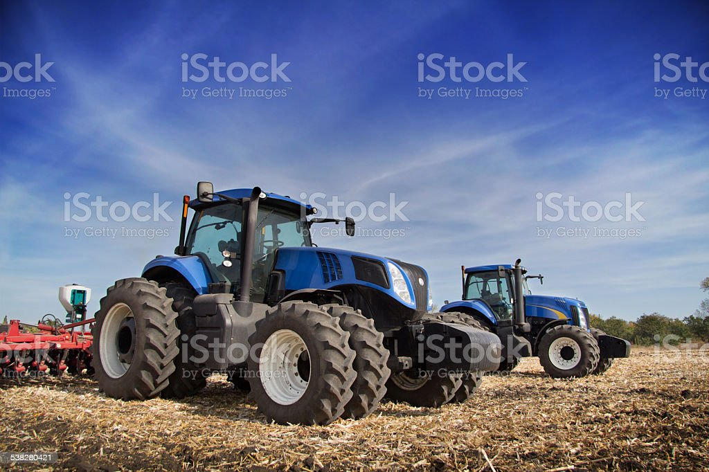 Two tractor drills in the field stock photo