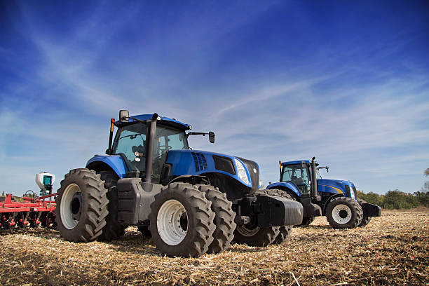 Two tractor drills in the field Two blue tractor with drills in the field under blue sky agricultural machinery stock pictures, royalty-free photos & images