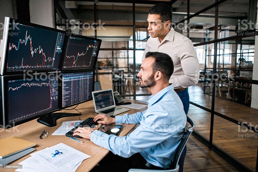 ファンド交換でグローバル通貨指数をチェックする2人のトレーダー - 25-29歳のロイヤリティフリーストックフォト