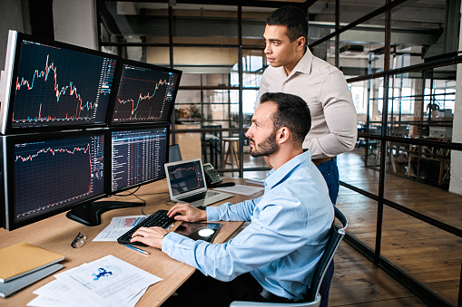 Two successful trader in formalwear working together in office, looking at screen, checking global currency index on fund exchange
