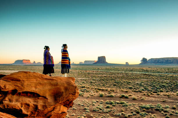 Two Traditional Navajo Native American Sisters In Monument Valley Tribal Park on a Rocky Butte Enjoying a Sunrise or Sunset Pretty Navajo girls wrapped in handwoven traditional blankets enjoying a grand sunrise or sunset in Monument Valley indigenous peoples of the americas stock pictures, royalty-free photos & images
